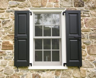If the windows are already wrapped with trim, consider mounting the shutter on top of the trim and using a decorative shutter hinge.